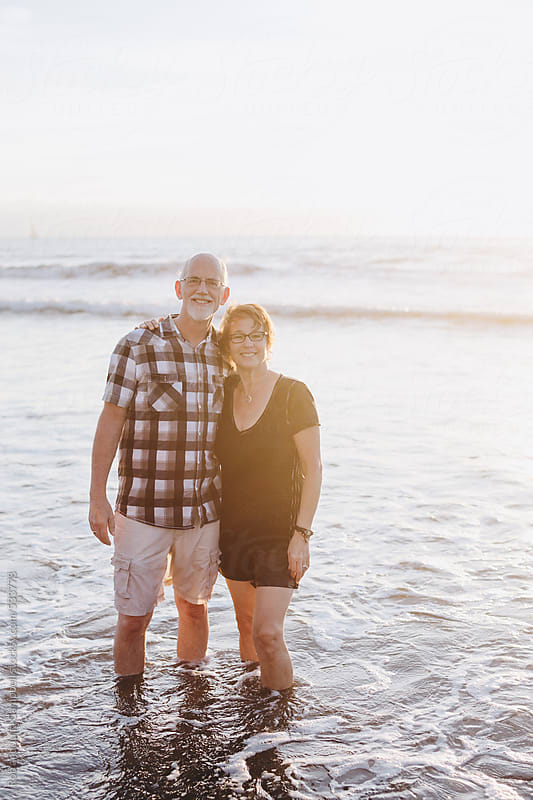 Content middle aged, retired couple smiling together outside on ocean beach by Rob and Julia Campbell for Stocksy United