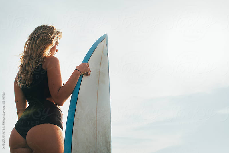 Rio de Janeiro - Pretty Blond Female Surfer Girl Standing Next to Surfboard in Warm Morning Light by VISUALSPECTRUM for Stocksy United