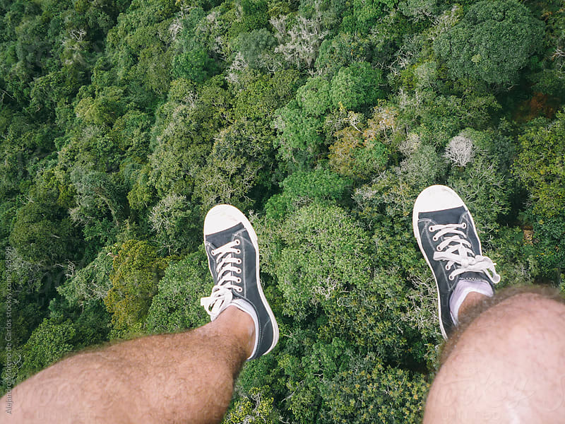 Dangling feet pov view of paragliding adventure over forest by Alejandro Moreno de Carlos for Stocksy United
