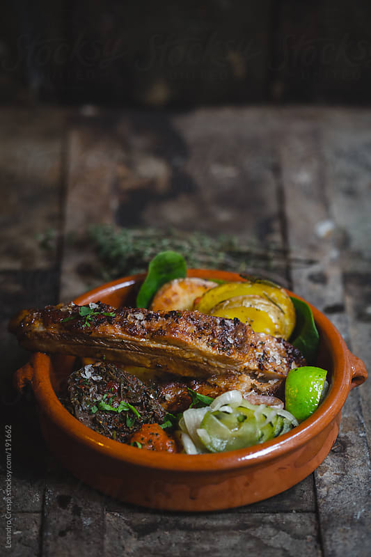 Barbecue pork ribs with oven roasted potatoes, cucumber pickle and marinated aubergine by Leandro Crespi for Stocksy United