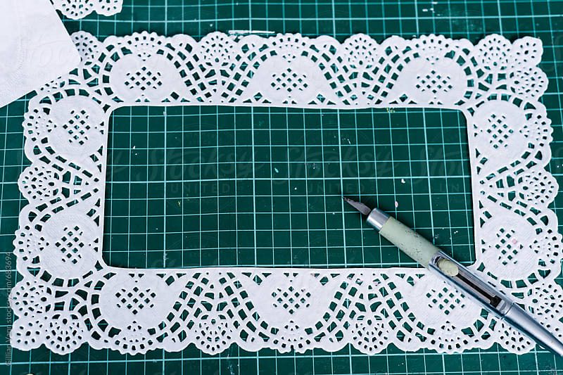 craft cutting mat with paper doily and scalpel knife by Gillian Vann for Stocksy United