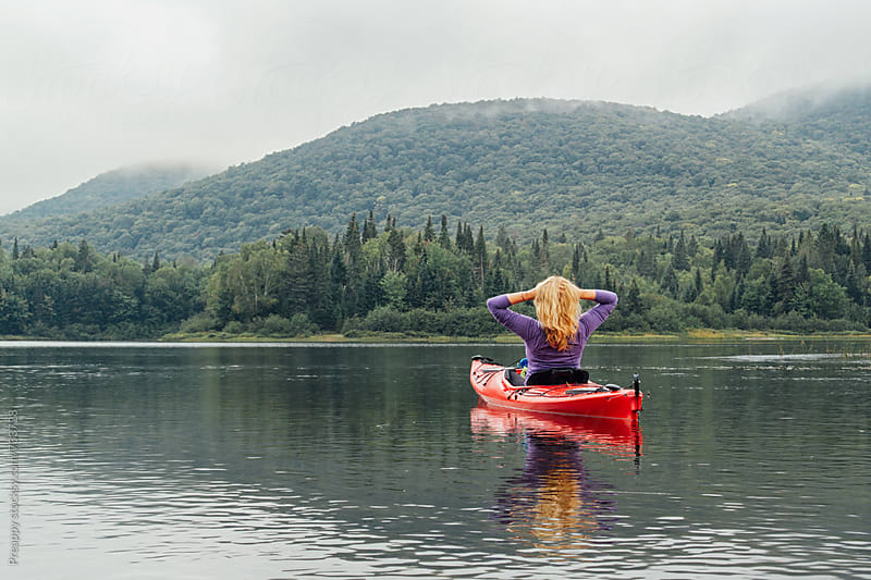 Woman sitting in kayak on water by Preappy for Stocksy United