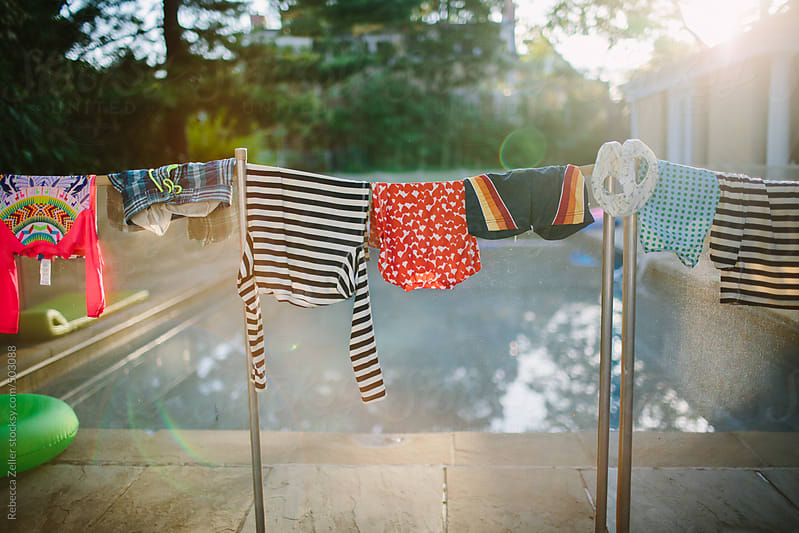 childrens' swimsuits hang to dry beside a pool in the summertime by Rebecca Zeller for Stocksy United