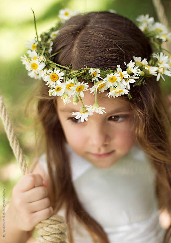 Child with flower wreath on her head by Dejan Ristovski for Stocksy United