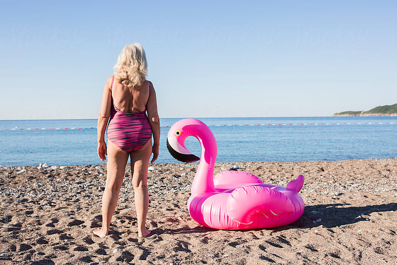 Elderly woman and flamingo on the beach by Jovana Rikalo for Stocksy United