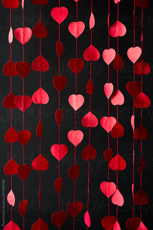 Diy red hearts curtain over black background by Pixel Stories for Stocksy United