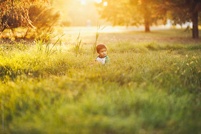 Asian Boy Playing in the Grass by Lumina for Stocksy United
