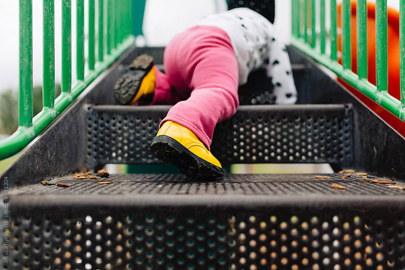 Small child climbing up stairs at playground by Jessica Byrum for Stocksy United