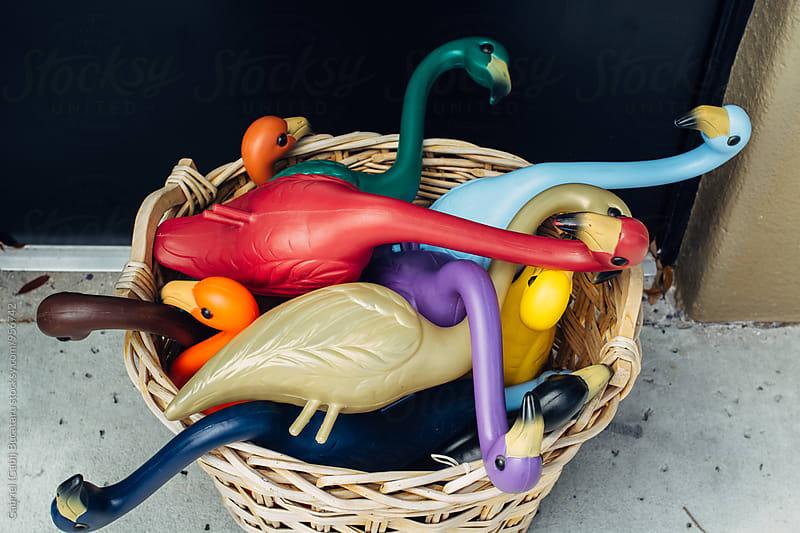 Plastic flamingos in a wicker basket by Gabriel (Gabi) Bucataru for Stocksy United