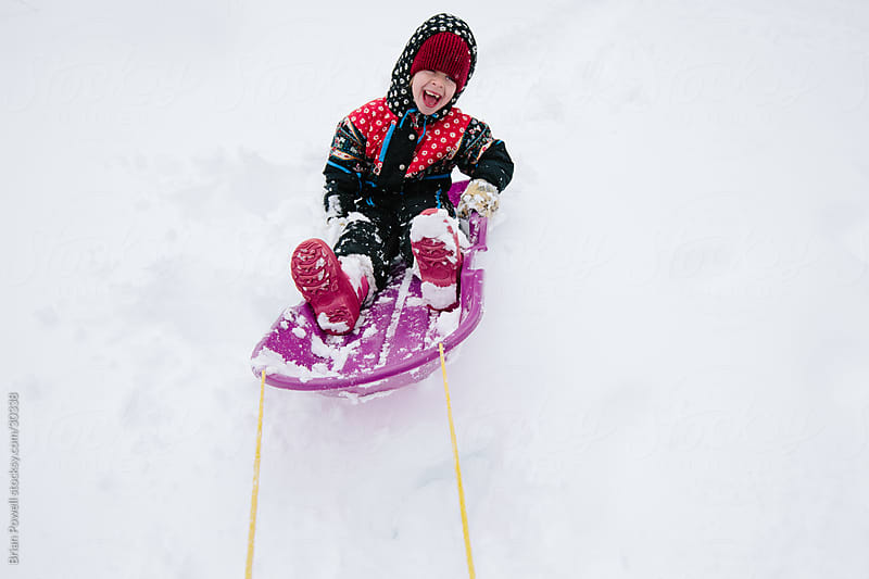 little girl being pulled on a sled by Brian Powell for Stocksy United