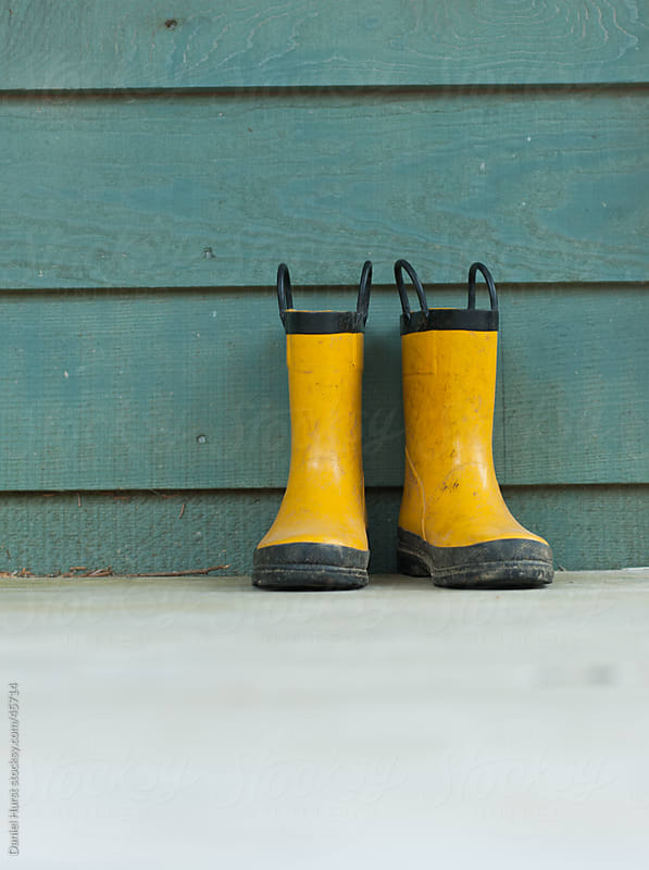 Yellow boots sitting up against wall by Daniel Hurst for Stocksy United