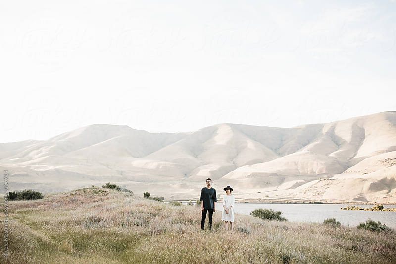 modern fashionable couple posing in desert landscape by Nicole Mason for Stocksy United