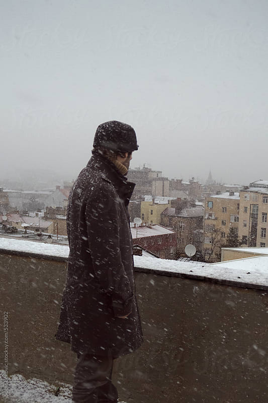 man from the back looking at the city in snow by Sonja Lekovic for Stocksy United