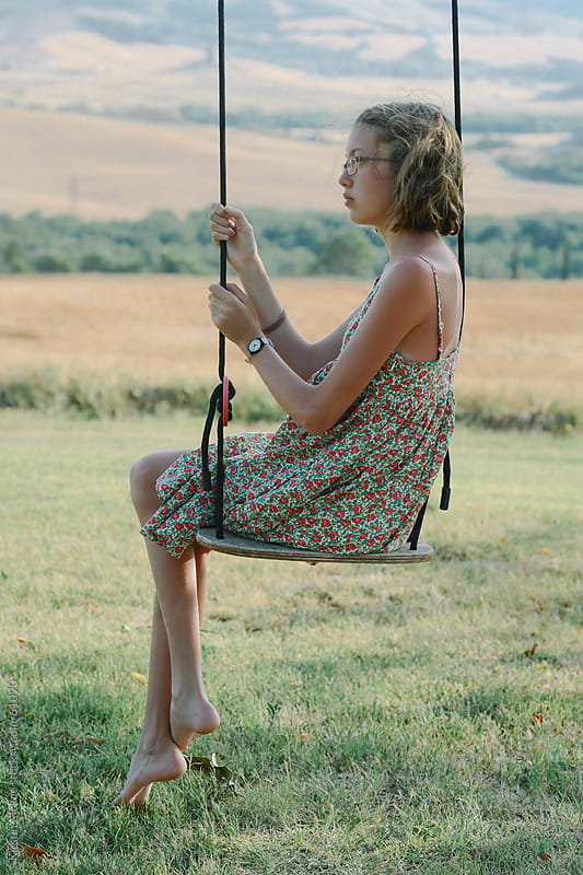 Girl sitting on swing with her legs crossed, with view of Tuscany behind.  by Kirstin Mckee for Stocksy United