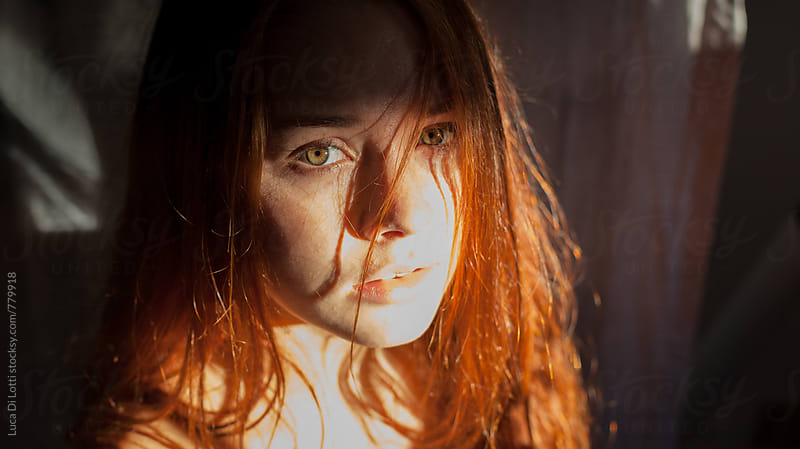 Portrait of a young beautiful woman with red hair and green eyes in a sunbeam by Luca Di Lotti for Stocksy United