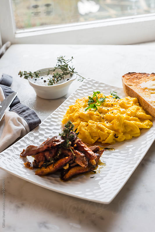 scrambled eggs with sauteed pine mushrooms by Gillian Vann for Stocksy United