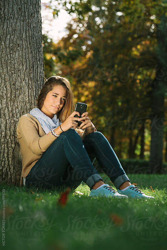 Cute Teenager Using a Cell Phone by VICTOR TORRES for Stocksy United