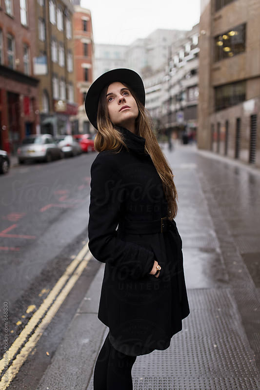 Woman dressed in a black coat and a hat in the street by Lucas Ottone for Stocksy United