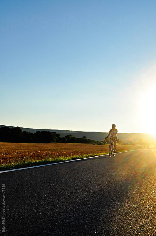 Woman Bikes on open road in rural setting with sunburst behind her. by Brian McEntire for Stocksy United