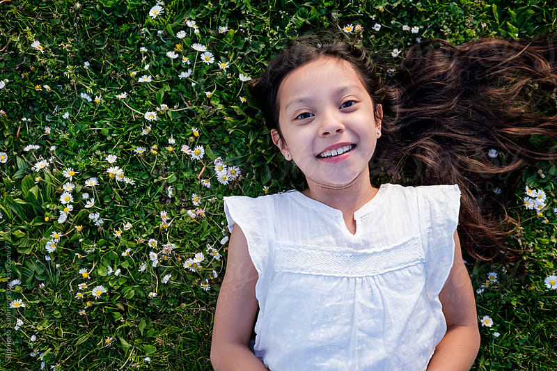 Happy mixed race girl lying down on the grass by Suprijono Suharjoto for Stocksy United