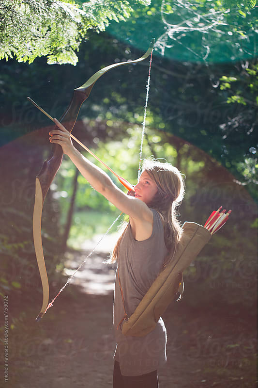 Young woman practicing archery outdoors by michela ravasio for Stocksy United