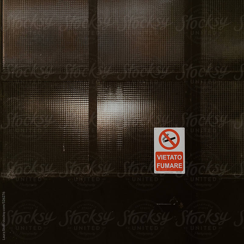 No smoking sign on iron and glass industrial  door by Laura Stolfi for Stocksy United