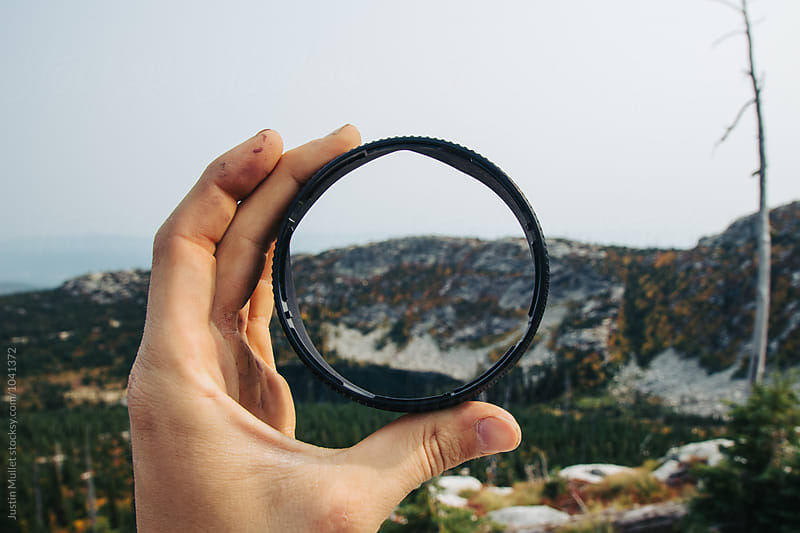 Man holding lens hood in front of mountain wilderness.  by Justin Mullet for Stocksy United