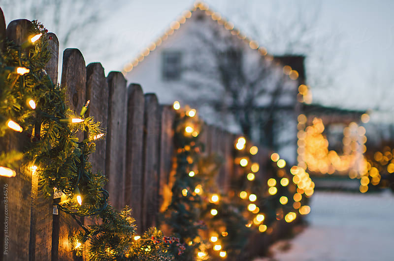 Holiday lights and garland adorn wooden fence by Preappy for Stocksy United