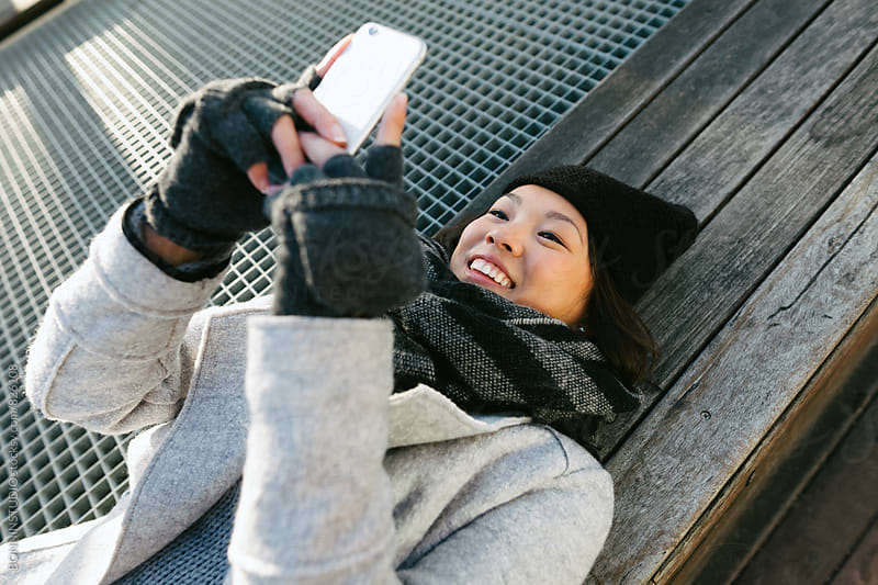Asian woman using her phone resting in a bench on winter. by BONNINSTUDIO for Stocksy United