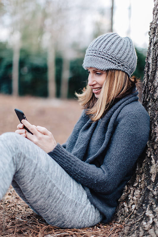 Beautiful woman sitting against a tree using her smartphone  by Jakob for Stocksy United