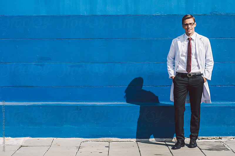 A wide shot portrait of a young professional man in front of a blue wall by Jovo Jovanovic for Stocksy United