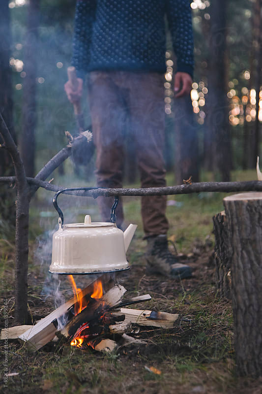 Old kettle hanging on branch above campfire by Danil Nevsky for Stocksy United