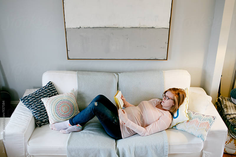 Pregnant woman lies on couch by Jen Brister for Stocksy United