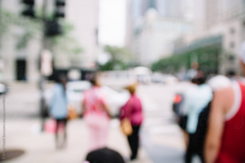 Out of focus people walking acros an intersection in a city by Gabriel (Gabi) Bucataru for Stocksy United
