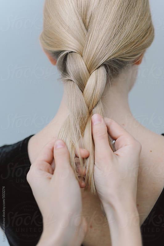 Woman braiding hair by Lyuba Burakova for Stocksy United