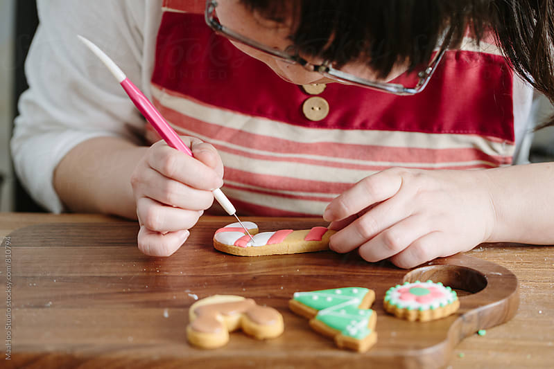 Young woman decorating christmas cookies by Maa Hoo for Stocksy United