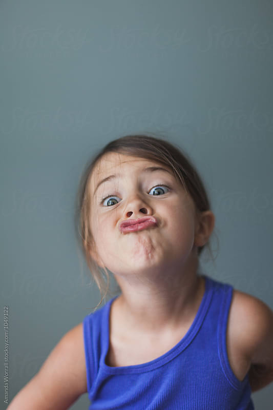 Simple indoor portrait of young girl making a silly face by Amanda Worrall for Stocksy United