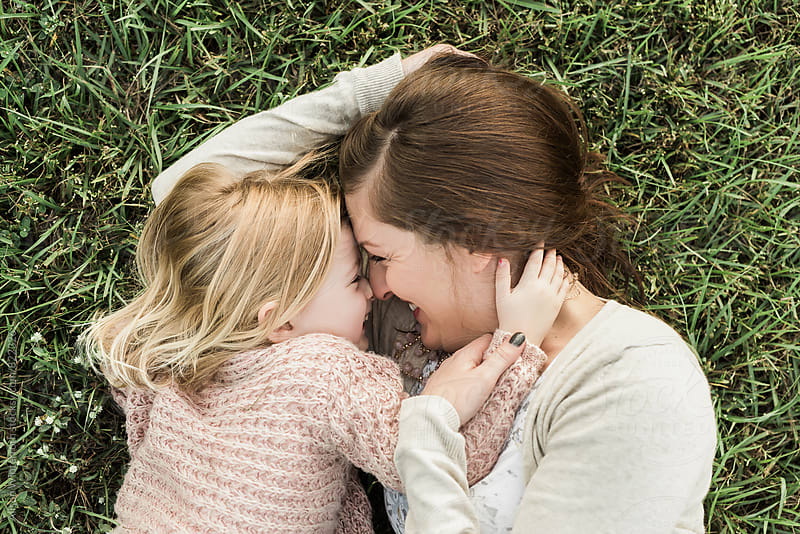 Mother And Daughter Laying On The Ground by Alison Winterroth for Stocksy United