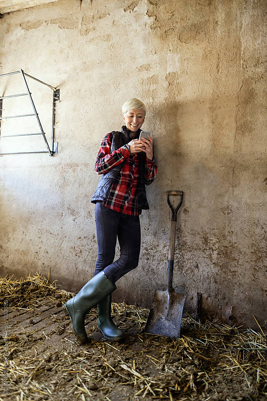 Woman farmer taking a break and using her phone on farm. by BONNINSTUDIO for Stocksy United