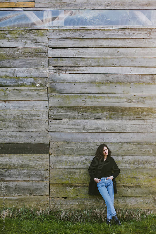 Brunette woman standing in front of a wooden wall by Marija Kovac for Stocksy United