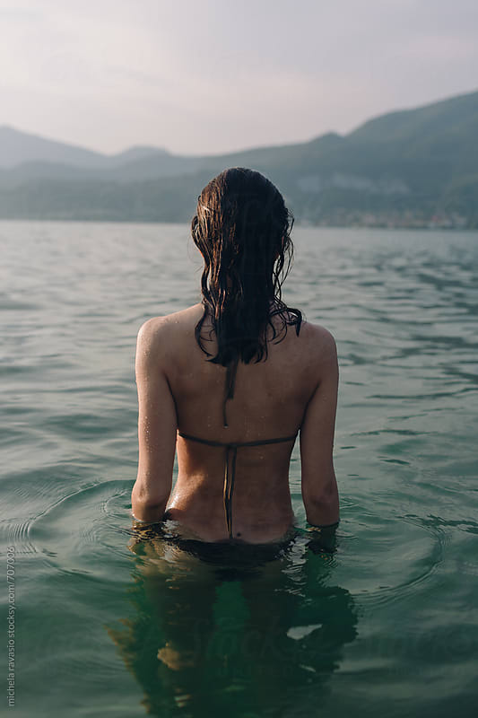 Woman in the water looking at the landscape at sunset by michela ravasio for Stocksy United
