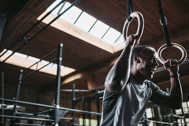 Young, fit black man laughing hard in fitness gym - rings by Rob and Julia Campbell for Stocksy United