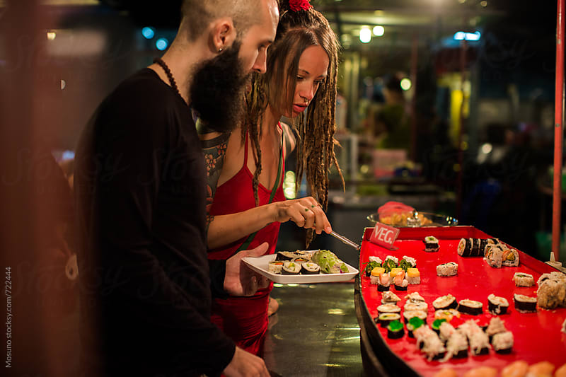 Man and Woman Buying Sushi at the Night Market by Mosuno for Stocksy United