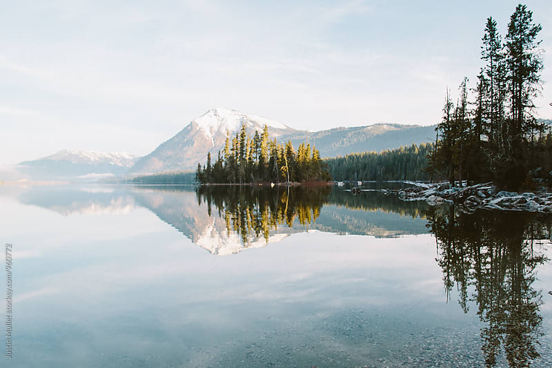 Sunrise light on a still mountain lake illuminating an island by Justin Mullet for Stocksy United