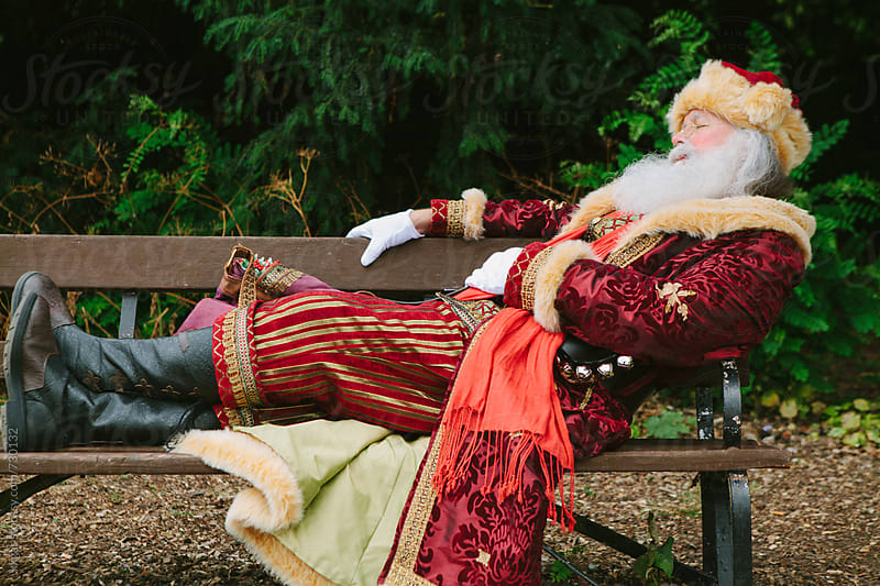 Santa Claus taking a nap on a park bench by kkgas for Stocksy United