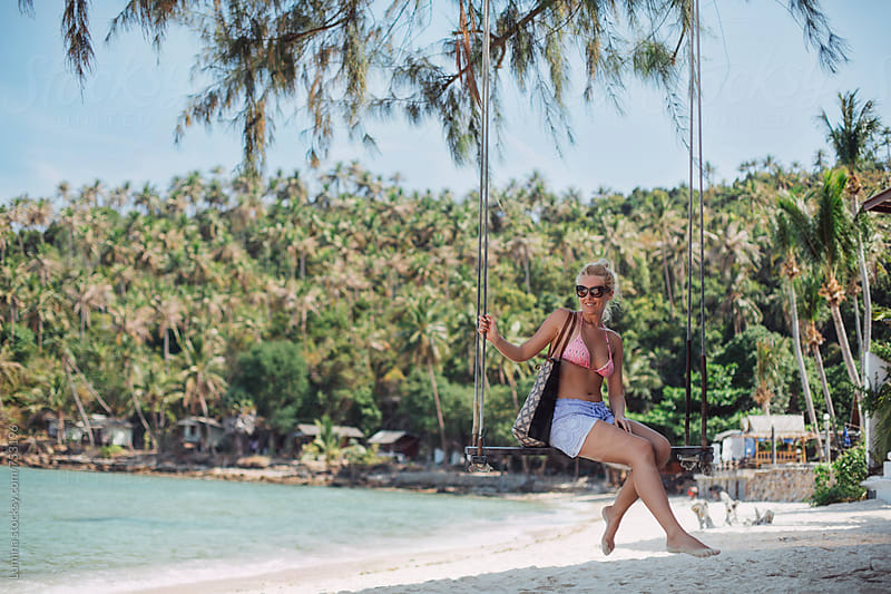 Happy Blonde Woman Sitting on a Swing on a Tropical Beach by Lumina for Stocksy United