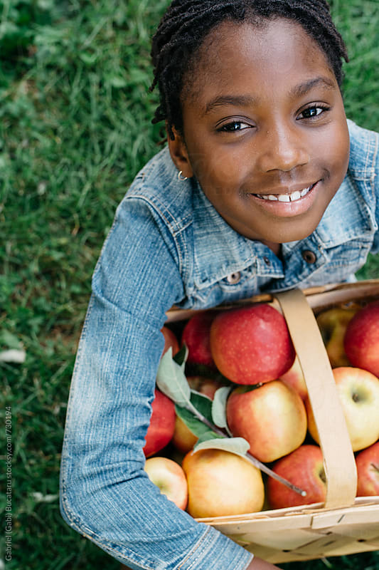 Smiling black girl holding a basket with apples by Gabriel (Gabi) Bucataru for Stocksy United