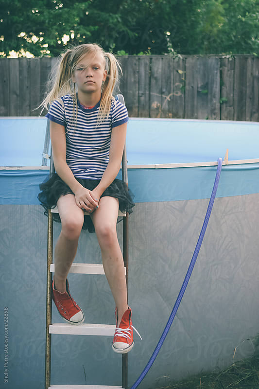 A Girl Sitting on Backyard Pool Ladder Disheveled in a Tutu and Sneekers by Shelly Perry for Stocksy United