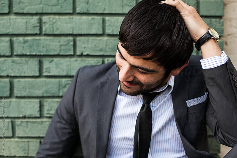 Man in a suit wearing a tie looking away from camera by J Danielle Wehunt for Stocksy United