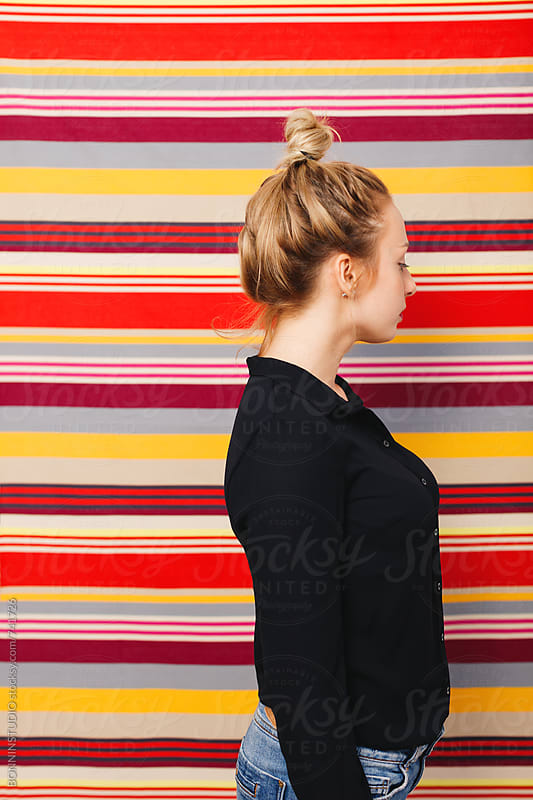 Side view of a woman standing in front of a striped wall. by BONNINSTUDIO for Stocksy United